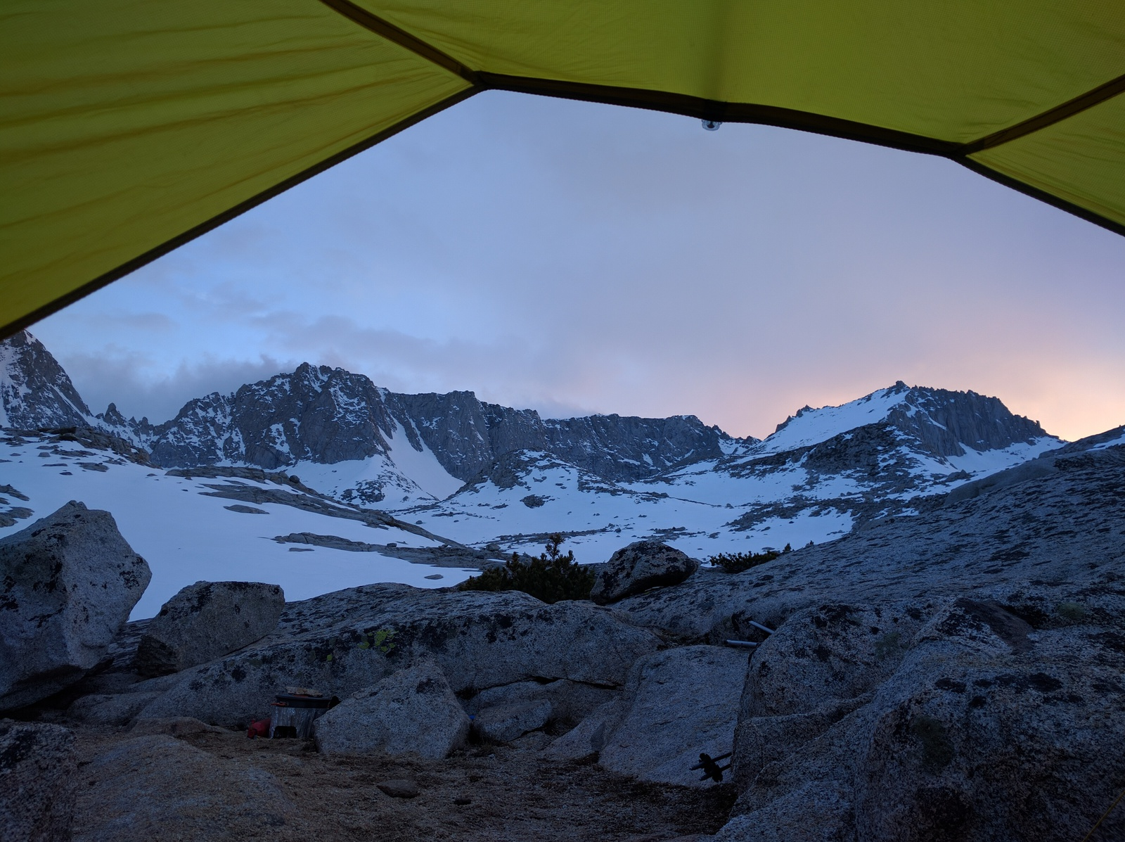 sunset-lit sky over the mountains, peering out of a tent
