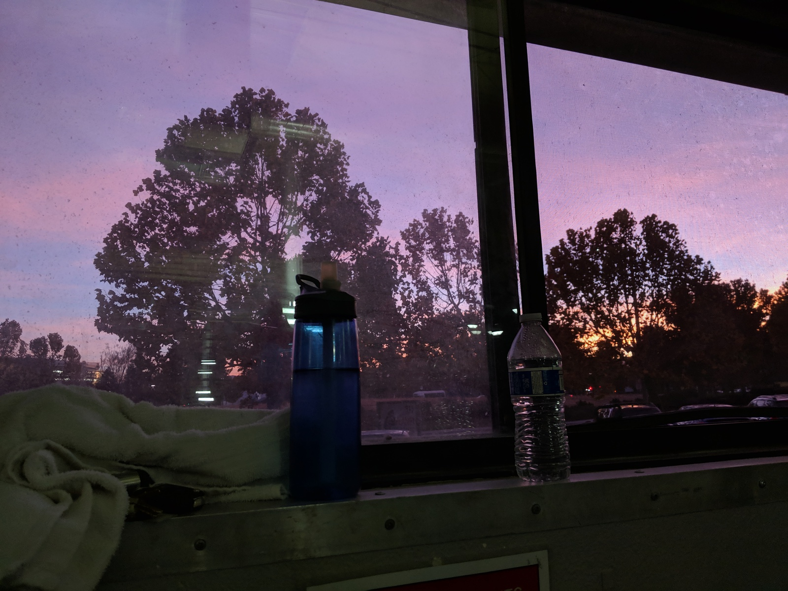 sunset-painted sky through a window, with water bottles and other gym accoutrements in the foreground